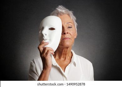 serious looking older woman revealing true face behind mask