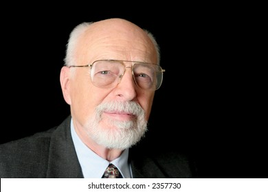 A serious looking senior man on a black background.