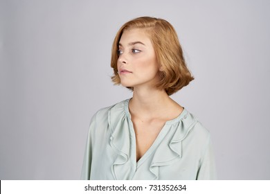 serious looking woman sideways on a light background studio