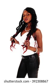 A serious looking young African American woman in white blouse andblack tights, holding her long black hair, isolated for white background.