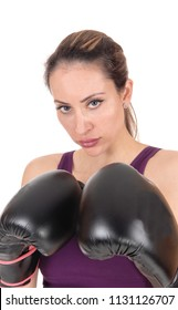 A serious looking young woman whit her black boxing gloves holding