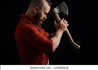 Serious lumberjack. Confident bearded man attached to forehead axe