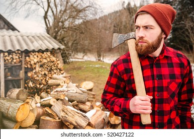 Serious lumberjack holding axe and looking away outdoors