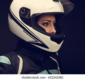 Serious makeup profile of rider woman looking in white motorcycle helmet and leather fashion protective jacket on black background. Closeup toned dark portrait of biker female