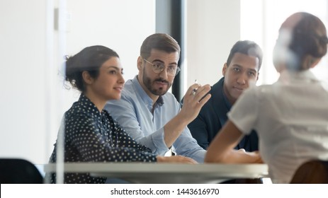 Serious male boss team leader hr recruiter talking to businesswoman client applicant at job interview or corporate briefing sit at table, businessman executive negotiating at diverse group meeting