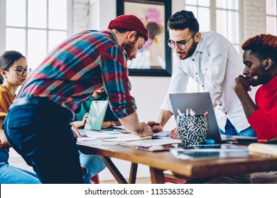 Serious male colleagues architect checking sketch and accountants working in team cooperate , multiracial crew of employees concentrated on project planning sitting at desktop and discussing ideas