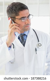 Serious male doctor using mobile phone in the hospital