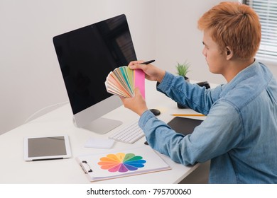 Serious male graphic designer looking at pictures in digital camera at office