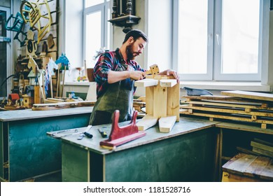 Serious male joiner in apron using tools for making furniture from wooden in workshop, concentrated owner of manufacturing business making crafts details by himself using instruments on working place
