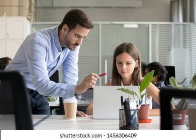 Serious male manager in glasses teach young female intern working at laptop, explain issues pointing, man trainer or coach instruct girl trainee helping with project, give instructions or correcting