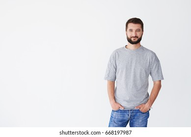 Serious male of middle age against clear background, holding hands in pockets of blue jeans, having beard, mid shot