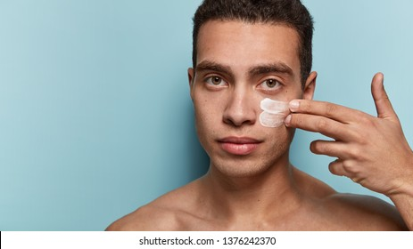 Serious male model with muscular body, applies face cream, cares of skin, stands against blue background, free space for your promotional content. Men, hygienic procedures, cosmetology concept
