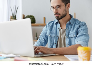 Serious male model wears denim shirt and glasses, checks emails online, uses modern laptop computer, works remotely on project, uses free wifi, keeps hands on keyboard, communicates with partners