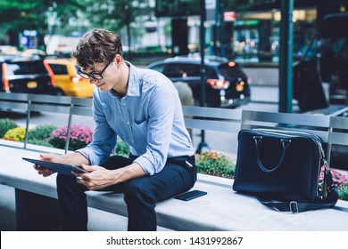 Serious male owner reading received notification with receipt on touch pad during time in financial district, businessman in formal wear using banking app digital tablet for checking balance account