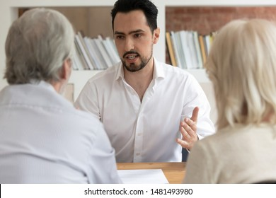 Serious male real estate agent talk with pensioner couple consulting about house property purchase or rent, man consultant or bank specialist speak help mature clients taking mortgage or loan