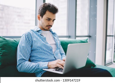 Serious male software developer working remotely on modern laptop device watching tutorial webinar online for certification training connected to 4g wireless for browsing internet on netbook