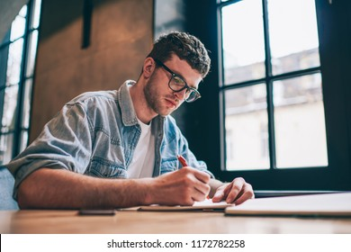 Serious male student writing essay sitting at desktop and spending time for course work, concentrated hipster guy doing school homework and planning study process, concept of education and knowledge