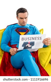 serious male superhero sitting on couch and reading business newspaper isolated on white