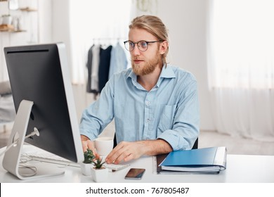 Serious male trader with blonde hair, beard, wearing glasses and blue shirt, prepares financial report on company`s income, typing on keyboard of computer, sits against modern light office interior.