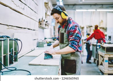 Serious male worker in protective safety wear making polish of wooden material with modern orbital grinder, skilled foreman concentrated on carpentry works sander timber in professional workshop