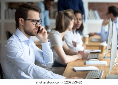 Serious male worker talk on phone consulting client in office, focused millennial employee speak on cell while working at computer in coworking workplace, man solving business problems online