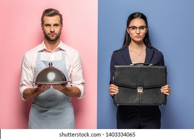 serious man in apron with Serving Tray and businesswoman with briefcase on blue and pink