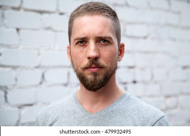 Serious man with a beard and mustache looking at the camera, white brick wall background
