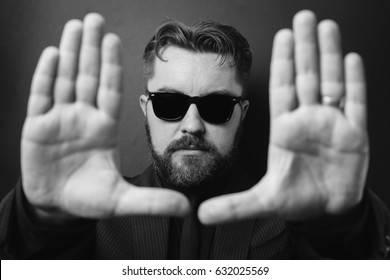 A serious man with a beard and a stylish hairstyle carries out framing with his hands. Directed in a business black suit and sunglasses. Black and white photo.