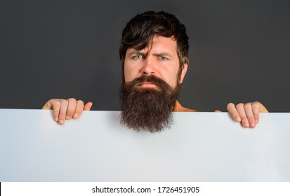 Serious man with blank board. Advertising banner. Ready for your text. Handsome man shows empty board. Space for your text. Bearded man holds empty board. Advertising board. Copy space for text.