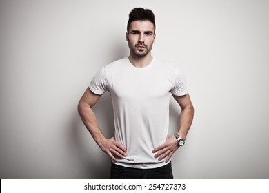 Serious man in blank t-shirt, white wall background