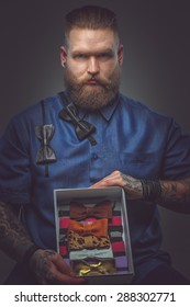 Serious man in blue shirt with bow ties collection. Isolated on grey