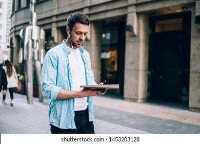 Serious man in casual wear listening useful audio book while walking at urban setting in city area using public internet connection, handsome hipster guy in electronic eyewear concentrated on record