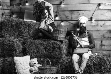 Serious man chef cook or baker with beard and moustache in hat toque and cute girl cookee teenager in apron sit on straw bales on rustic background.