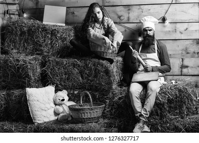Serious man chef cook or baker with beard and moustache in hat toque and cute girl cookee teenager in apron sit on straw bales on rustic background