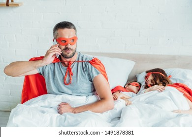 serious man in costume of superhero talking on smartphone while sitting in bed near sleeping wife and son