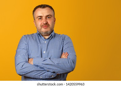 Serious man with folded arms and a deadpan expression posing in front of a yellow background. Copy space