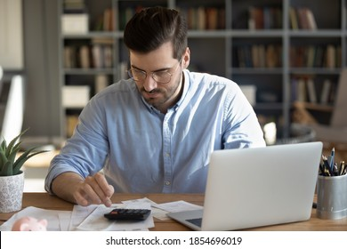 Serious man in glasses sit at workplace desk in office use calculator calculates monthly expenses, taxes, check bank account balance, summarize total sum. Family or personal budget management concept
