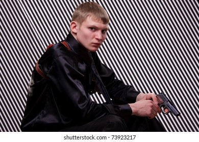 Serious man with a gun against striped background