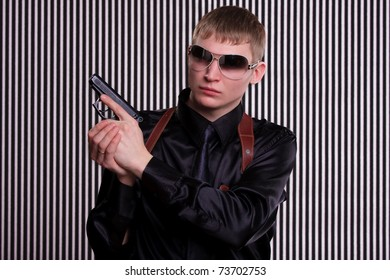 Serious man with a gun standing against striped background