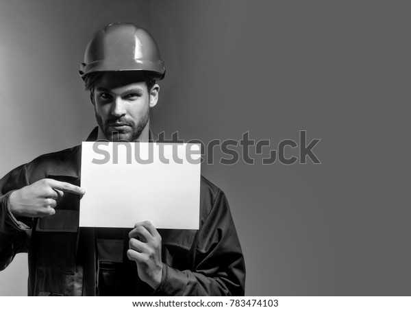 Serious man handsome builder construction mason worker repairman craftsman foreman bearded male in boilersuit and orange hard hat keeps blank paper for copy space in hands on grey background