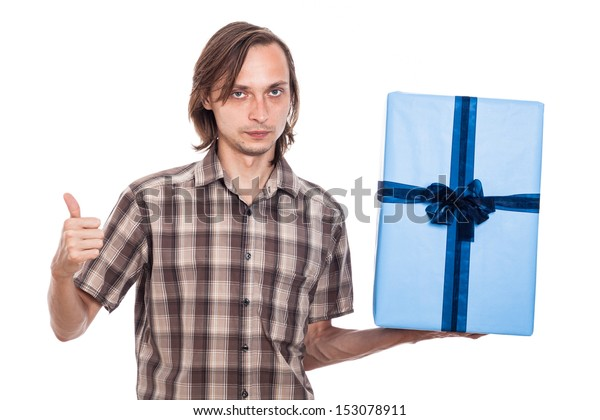 Serious man holding big blue gift box showing thumb up, isolated on white background