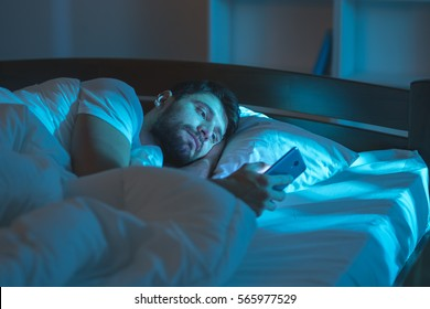 The serious man lay on the bed and phone at night