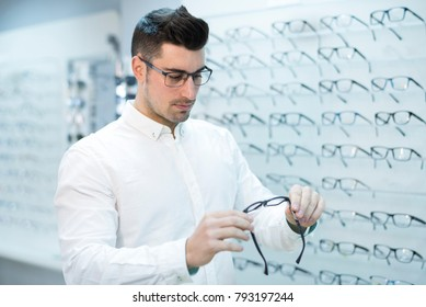 Serious man looking glasses frame in store