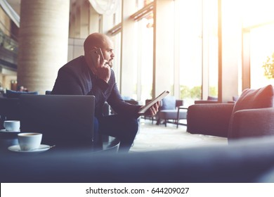 Serious man managing director of big prosperous company is holding touch pad and calling to manager to hear the explanation of why the client left a negative review about service on official website