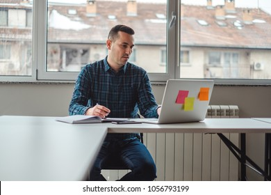 Serious man at the office  working on a laptop while holding a pen over notebook