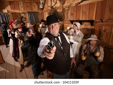Serious man with old west gang holding guns