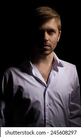 serious man on a black background in low key