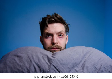 Serious man on blue background holding head on pillow and looking at camera, having trouble sleeping concept