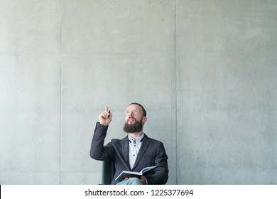 serious man pointing index finger and looking upward. business seminar corporate education.