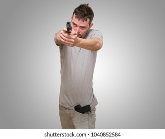 serious man ponting with gun against a grey background